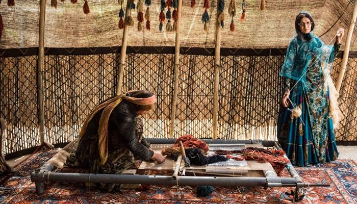 donne intente nella lavorazione di un tappeto